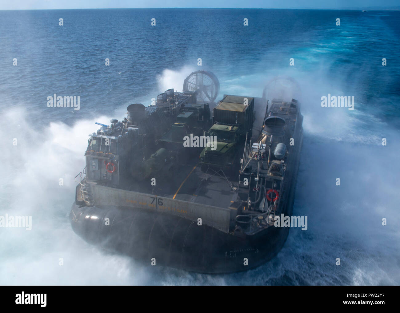 181010-N-DC385-1028 PACIFIC OCEAN (Oct. 10, 2018) Landing craft air cushion (LCAC) 76, assigned to Assault Craft Unit (ACU) 5, disembarks the well deck of the amphibious assault ship USS Bonhomme Richard (LHD 6). Bonhomme Richard is operating in the U.S. 3rd Fleet area of operations. (U.S. Navy photo by Mass Communication Specialist 3rd Class Cosmo Walrath) - Stock Image
