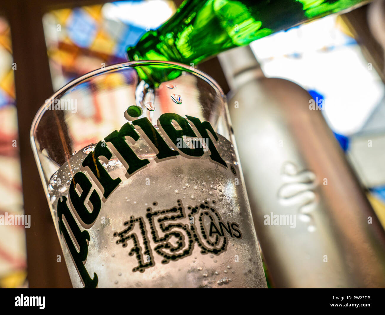 Sparkling chilled Perrier (150 ans) water pouring restaurant table situation, with stained glass window and old Town Vannes behind Brittany Finistere - Stock Image