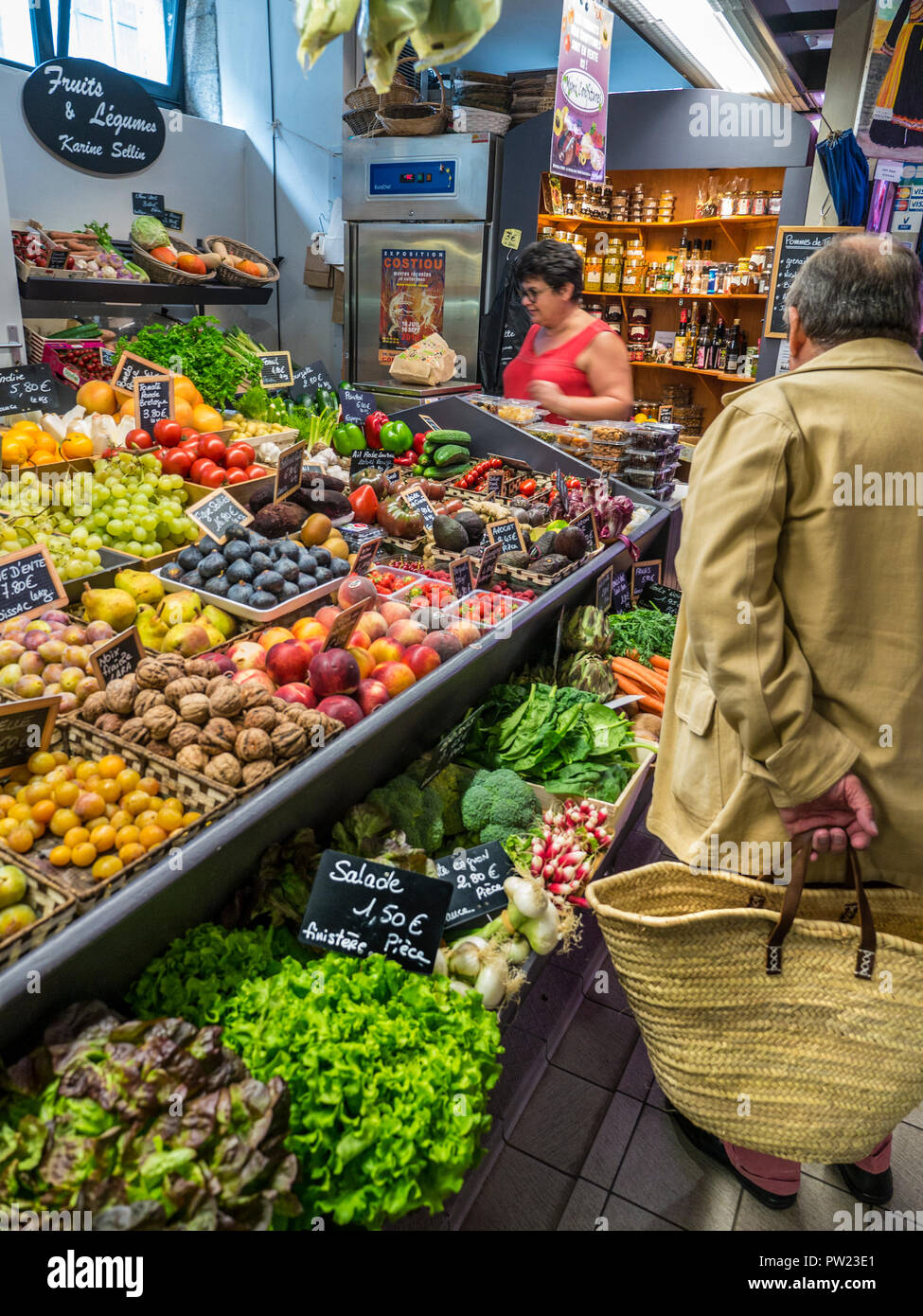 CONCARNEAU COVERED INTERIOR MARKET Fresh French Produce on sale French male shopper & bag in covered Halles market hall Concarneau Brittany France - Stock Image