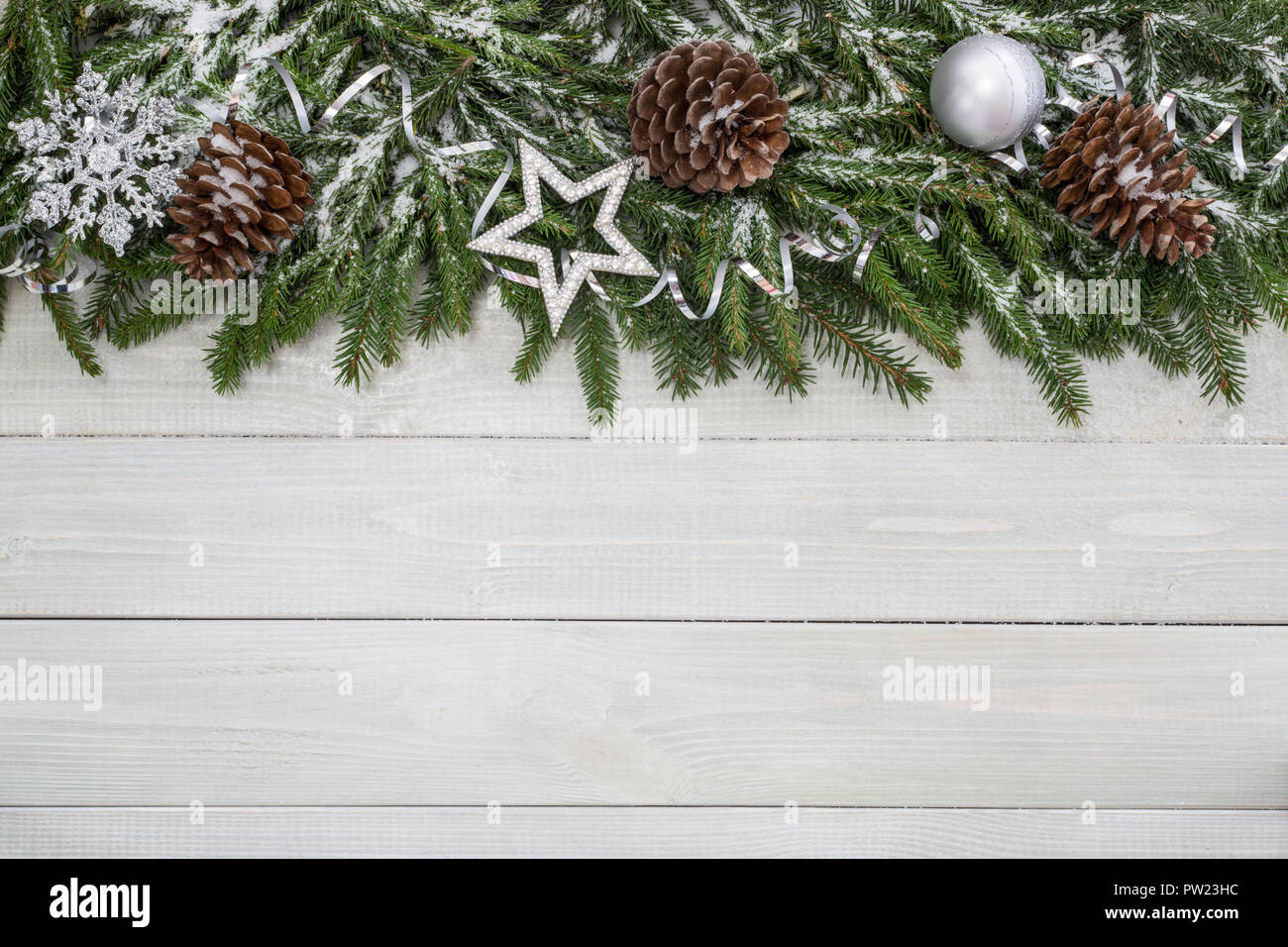 christmas background with fir branches decor and snow on white toned natural wooden plank background texture provence style for copy space for text