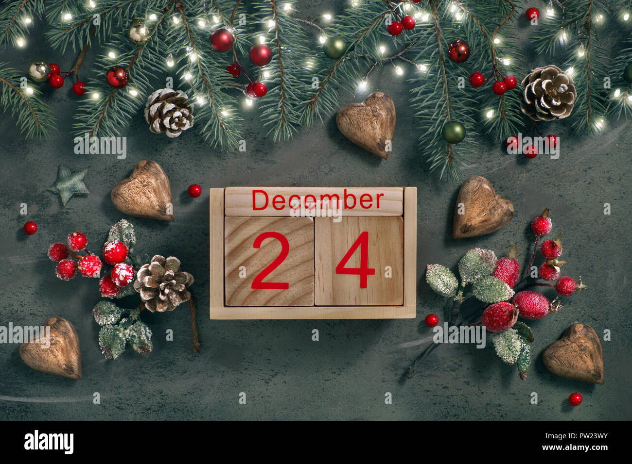 Christmas Eve Date On Calendar, December 24, with Christmas decorations and festive lights on fir twigs, frosted red berries and wooden hearts on gree - Stock Image