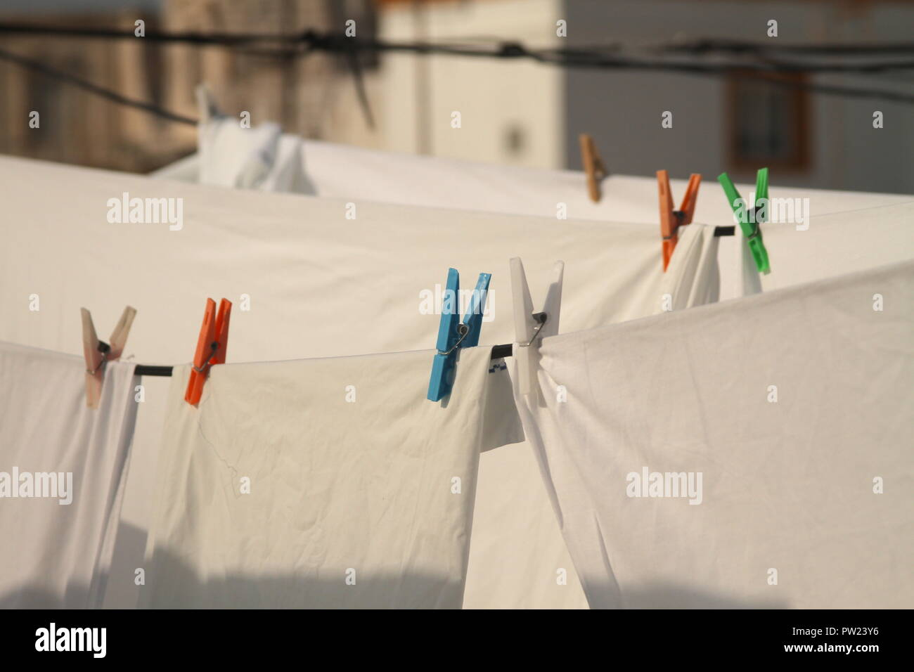 White sheets and clothes hanging clamped from drying lines, in a small Mediterranean town rooftop. - Stock Image