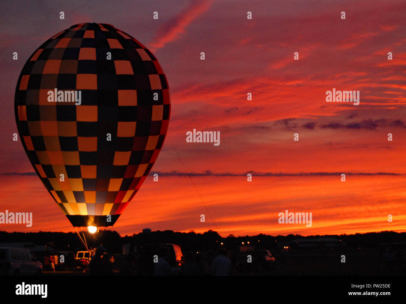 Pre-launch inflated hot air balloon on ground at sunset - Stock Image