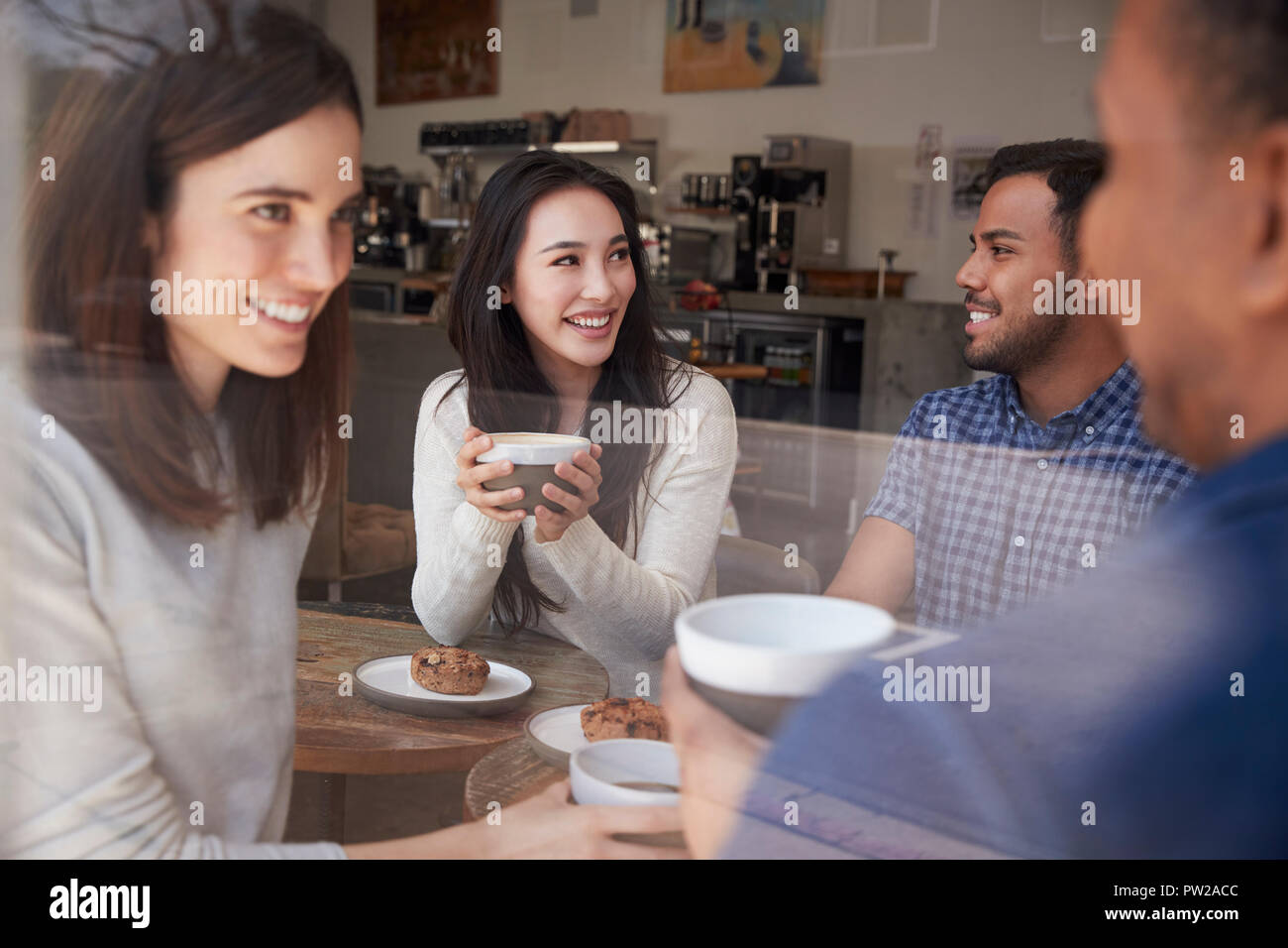 Four smiling adult friends sit having coffee at coffee shop Stock Photo