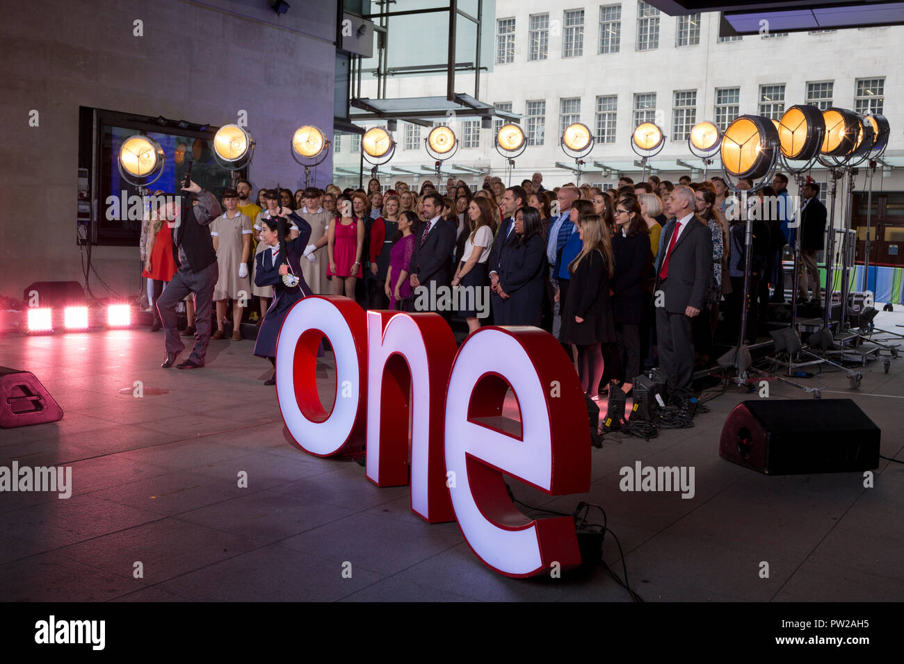 A choir rehearse a Mary Poppins song during an outside broadcast for the One Show at Broadcasting House, on 4th October 2018, in London, England. - Stock Image