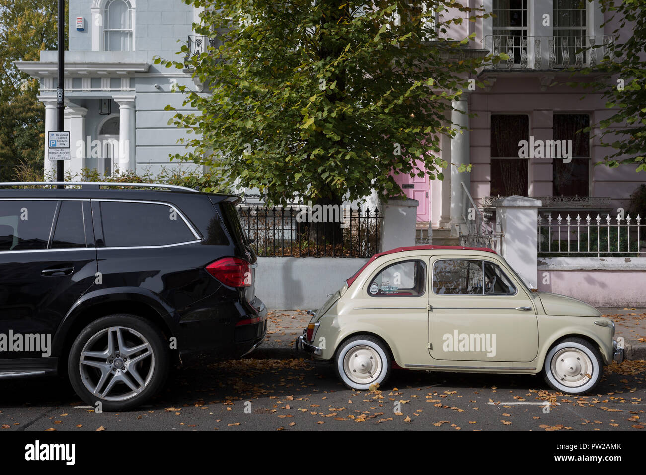 A large 4x4 SUV car parked behind a much smaller FIAT 500 among autumn leaves on Elgin Crescent in Notting Hill, on 7th October 2018, in London, England. - Stock Image