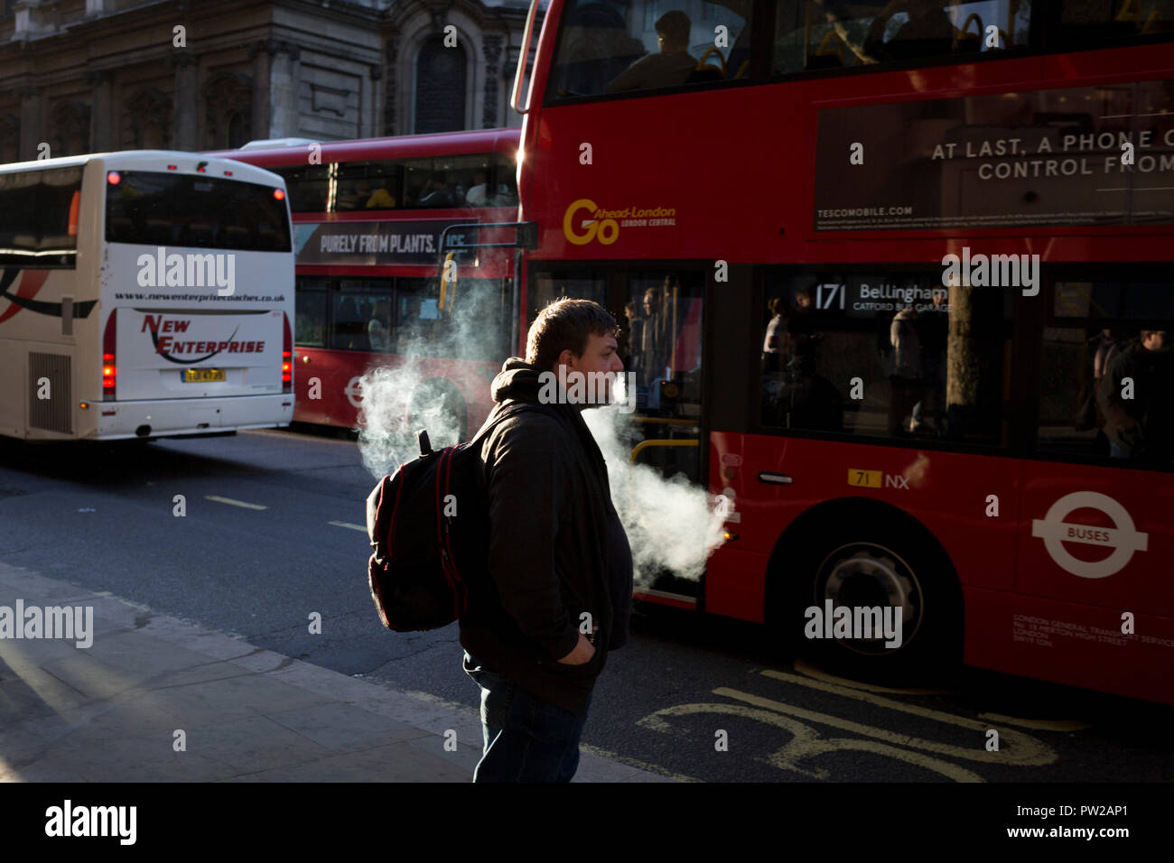 A vaper exhales before boarding a bus during the evening rush-hour in the capital, on 3rd October 2018, in London, England. - Stock Image