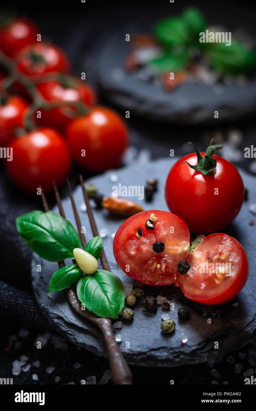 Frische Cherry Tomaten mit Basilikum auf Schiefer angerichtet - Stock Image
