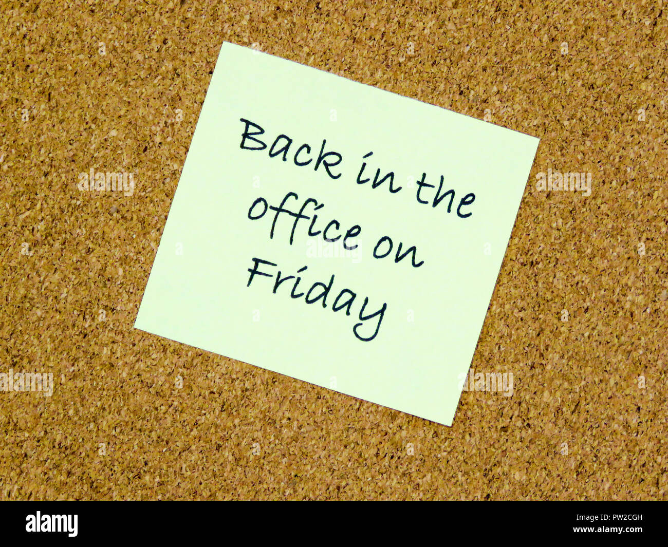 A yellow sticky note with back in the office on Friday written on it on a cork board background Stock Photo