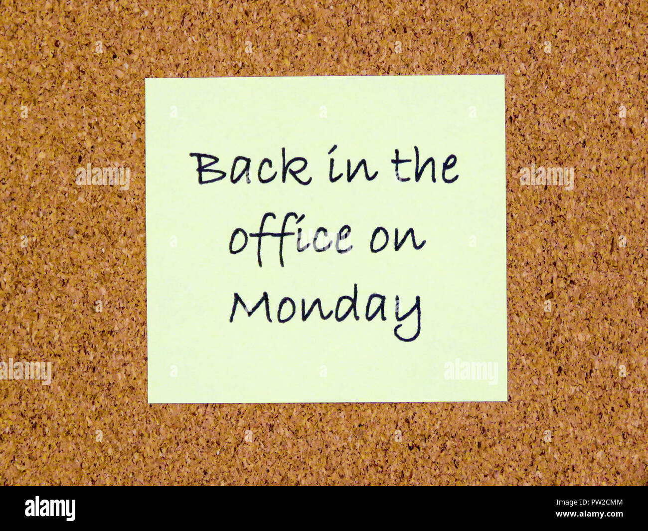 A yellow sticky note with back in the office on Monday written on it on a cork board background Stock Photo
