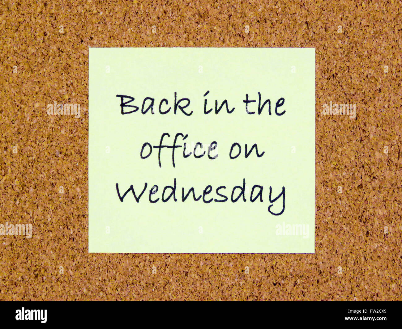 A yellow sticky note with back in the office on Wednesday written on it on a cork board background Stock Photo