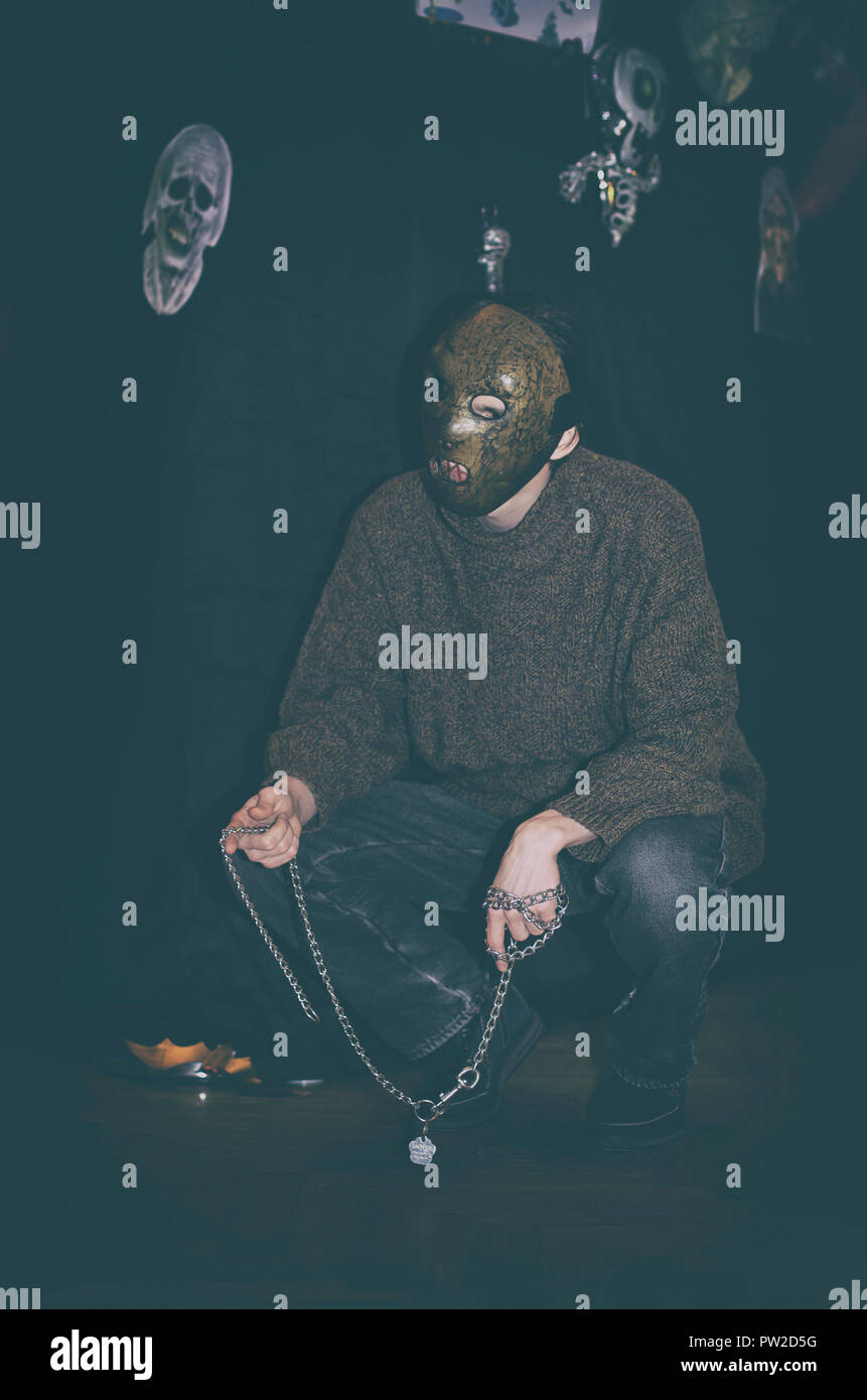 Maniac in a creepy mask. Stylized as a movie character from a horror movie on Halloween - Stock Image