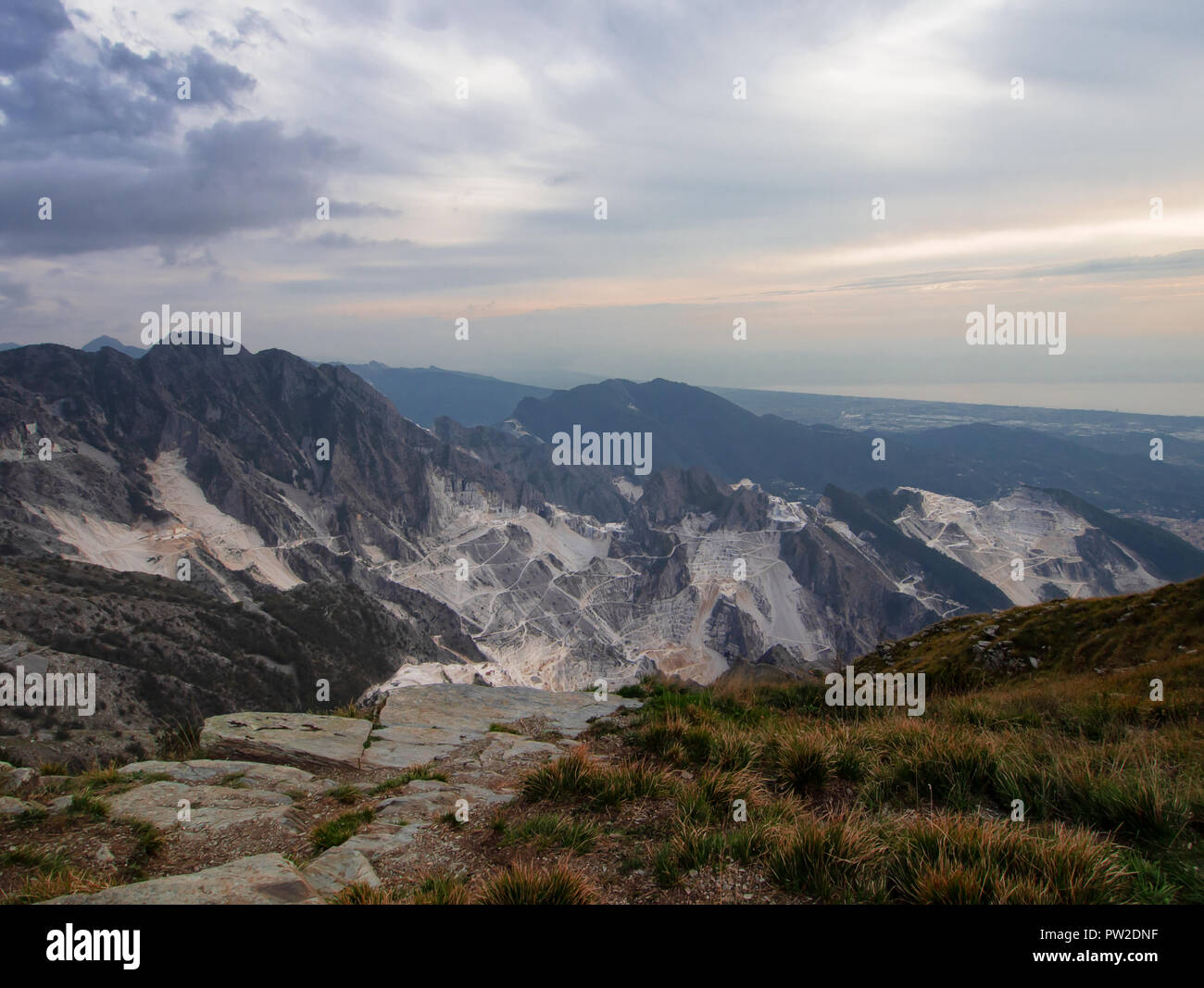 Dramatic wide angle view over the white marble quarries seen from Campo Cecina, Massa Carrara, Italy. Autumn, fall. Beautiful landscape but also environmental issues. - Stock Image