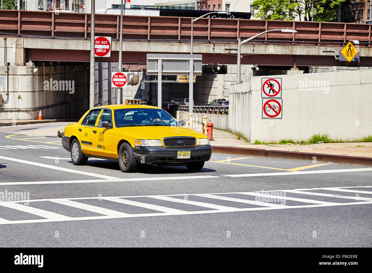 New York City, USA - June 28, 2018: Yellow taxi cab stops at zebra crossing. Stock Photo