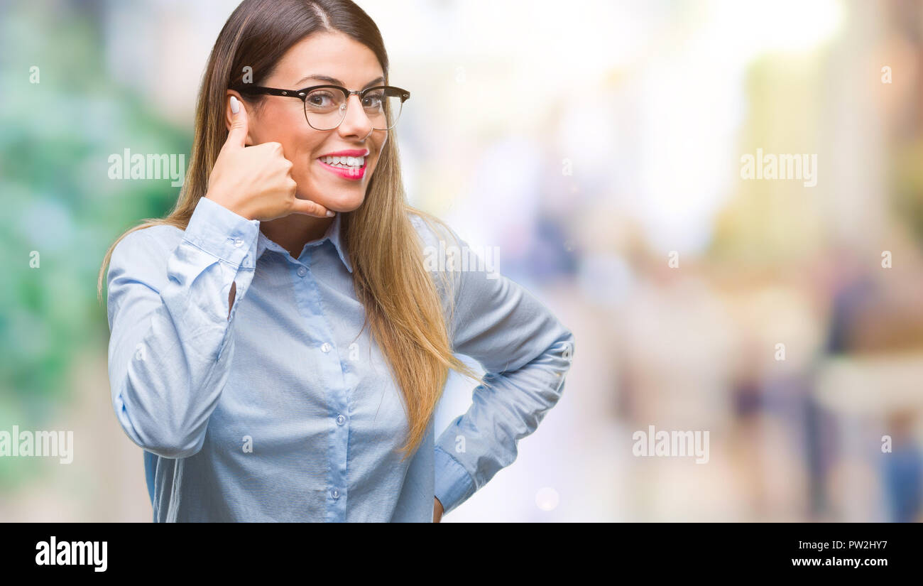 Young beautiful business woman wearing glasses over isolated background smiling doing phone gesture with hand and fingers like talking on the telephon - Stock Image