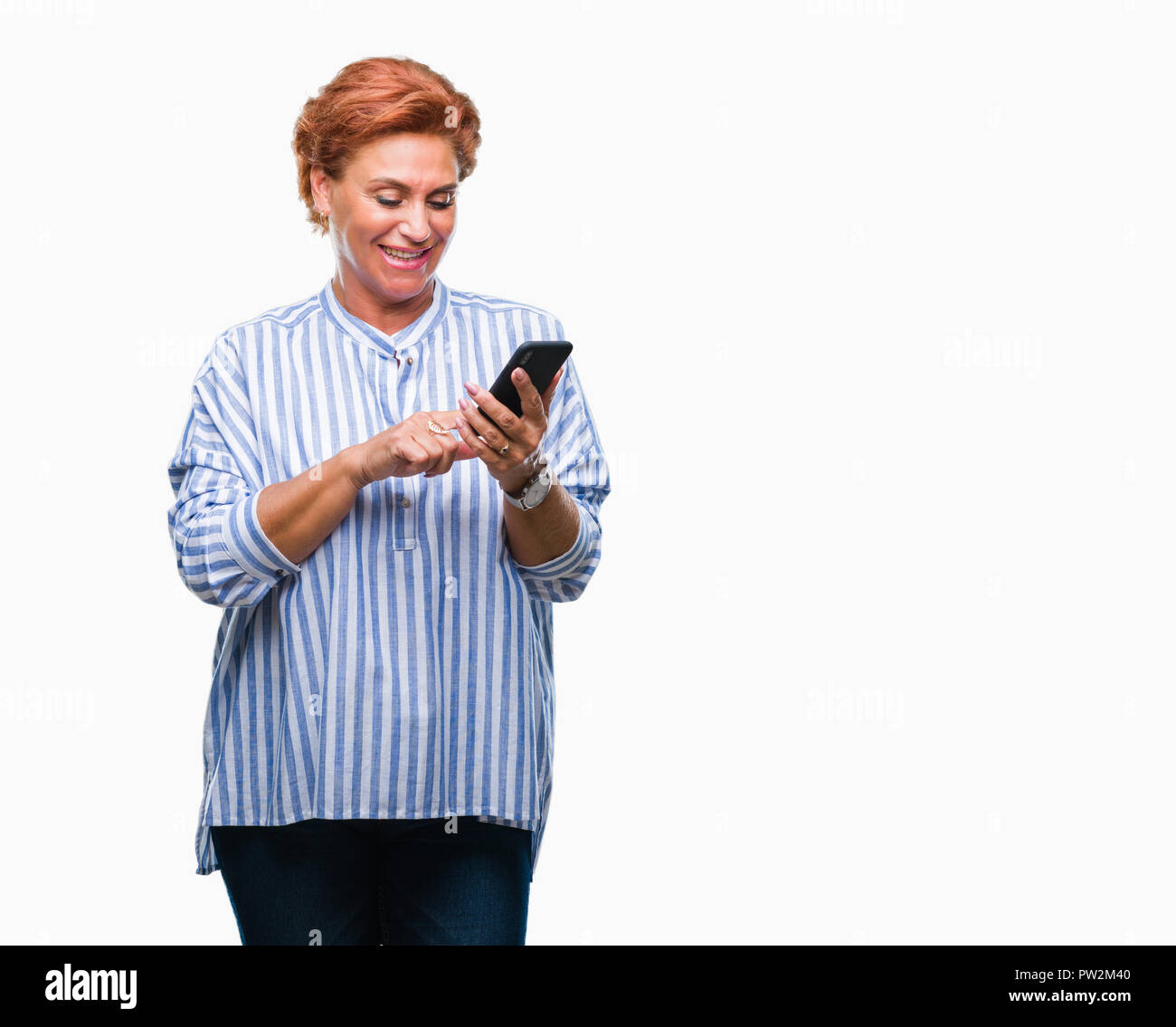Atrractive senior caucasian redhead woman texting using smartphone over  isolated background with a happy face standing