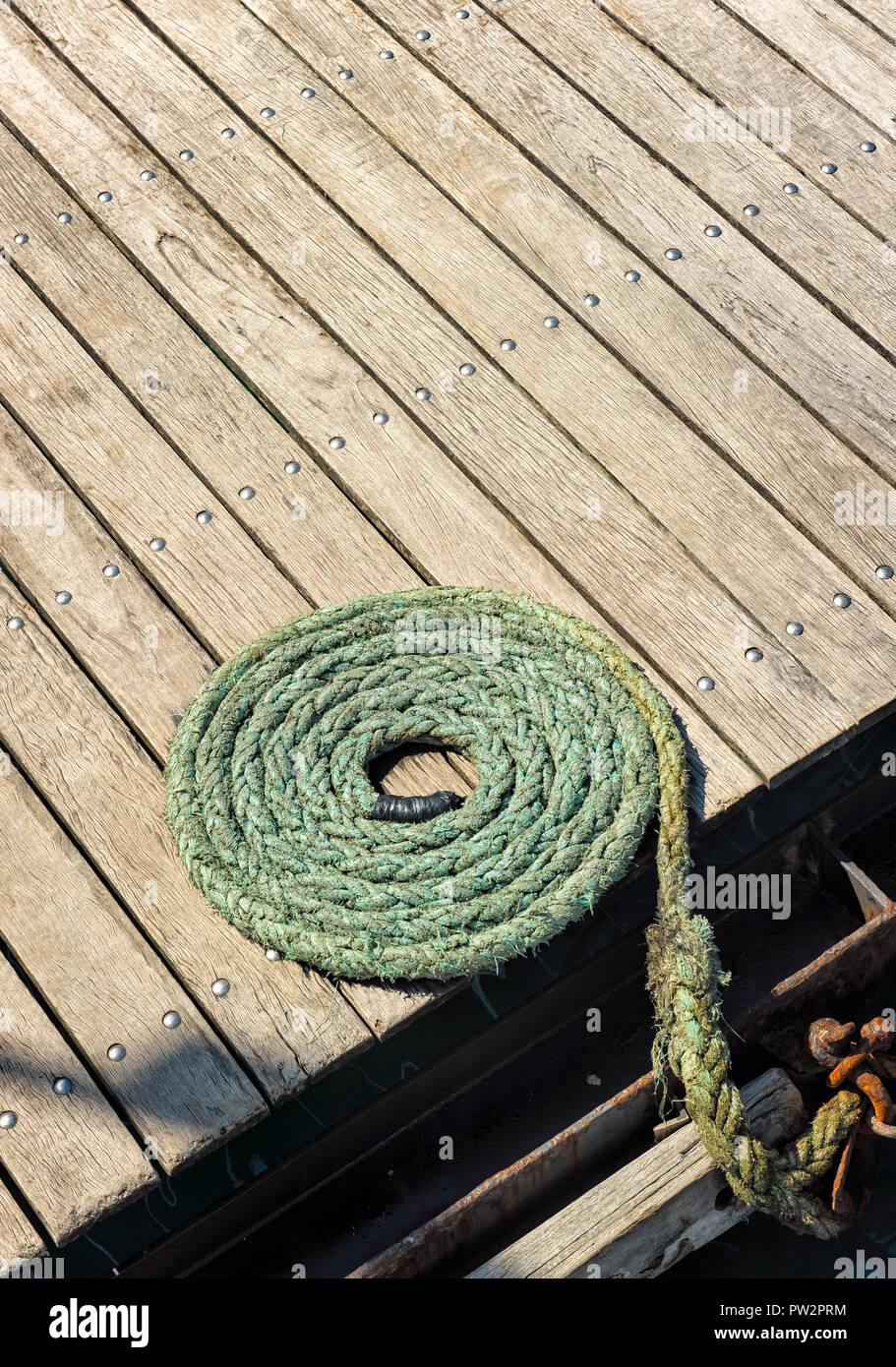 Patterned coil of mooring rope sits on the wooden deck of a wharf awaiting the next boat. - Stock Image