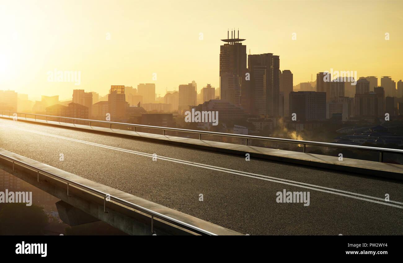 Empty asphalt flyover  road with modern cityscape skyline , sunrise scene . - Stock Image