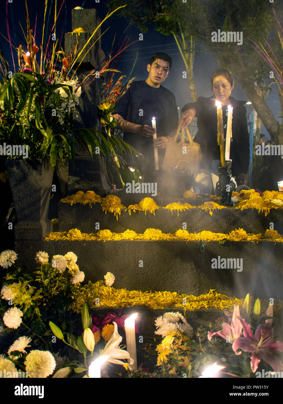 Men Remembering Loved Ones in the Historic Mixquic Cemetery in CDMX on the Day of the Dead - Stock Image