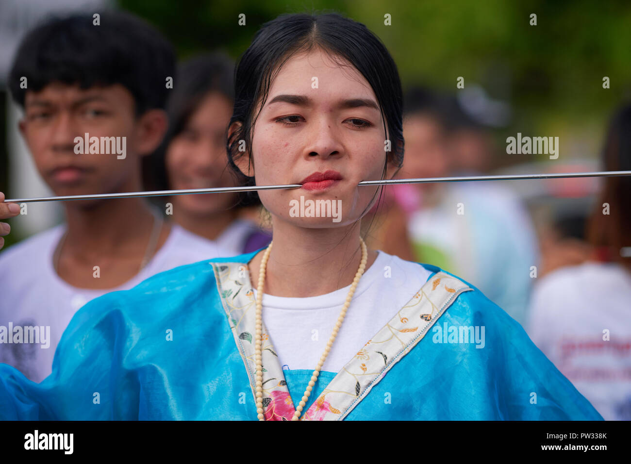 During the Vegetarian Festival in Phuket Town, Thailand, a woman in traditional Chinese dress and with pierced cheektakes on the role of spirit medium - Stock Image