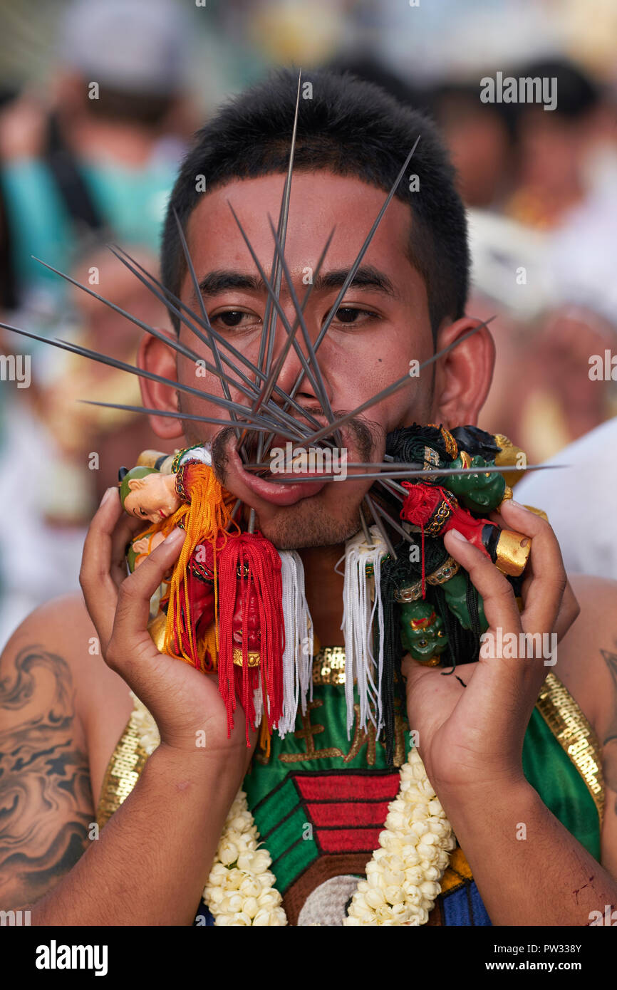 A street procession during the annual Vegetarian Festival in Phuket, Thailand, during which some participants pierce their bodies with strange objects - Stock Image