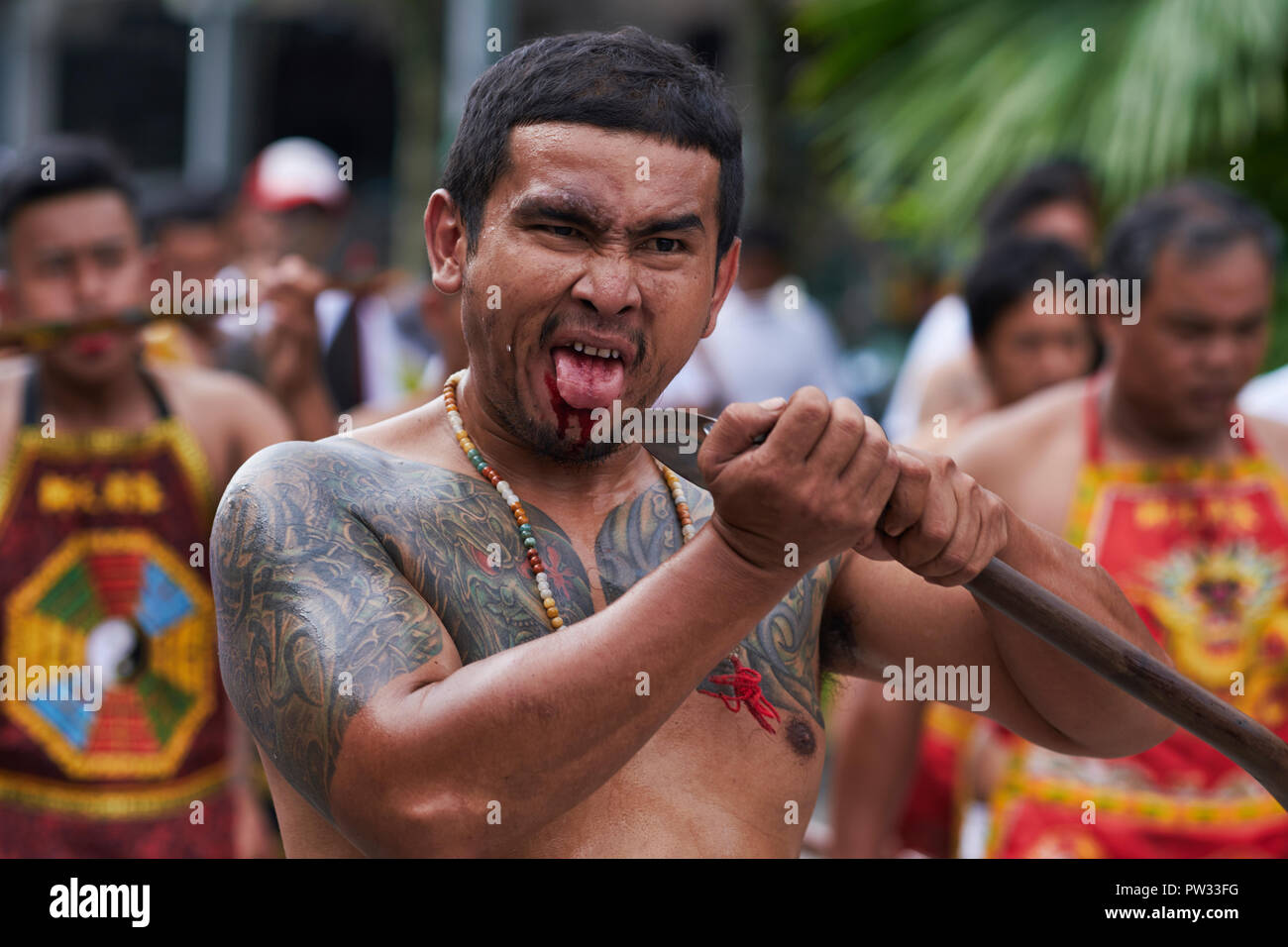 A street procession during the annual Vegetarian Festival in Phuket, Thailand, during which this participant repeatedly cuts his tongue - Stock Image