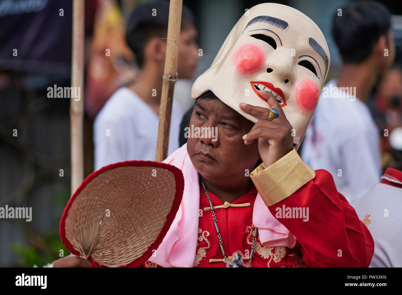 A participant in a procession during the Vegetarian Festival in Thalang, Phuket, Thailand, lifting his Chinese mask to reveal a gloomy face beneath - Stock Image