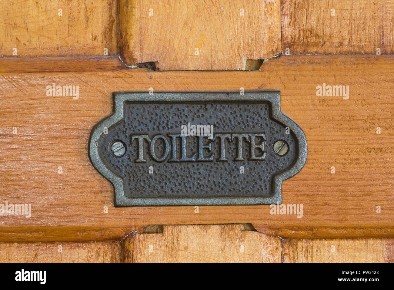 Close-up, metal sign with the inscription Toilette on wooden door, Canada - Stock Image