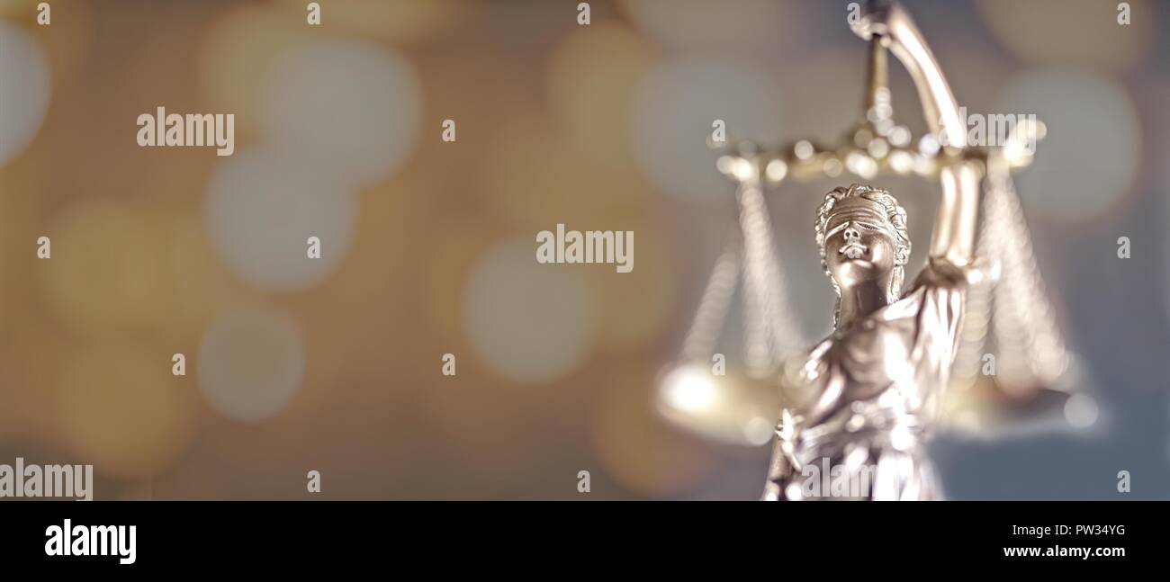 Closeup of golden lady Justice statue - focus on foreground with bokeh background - Stock Image