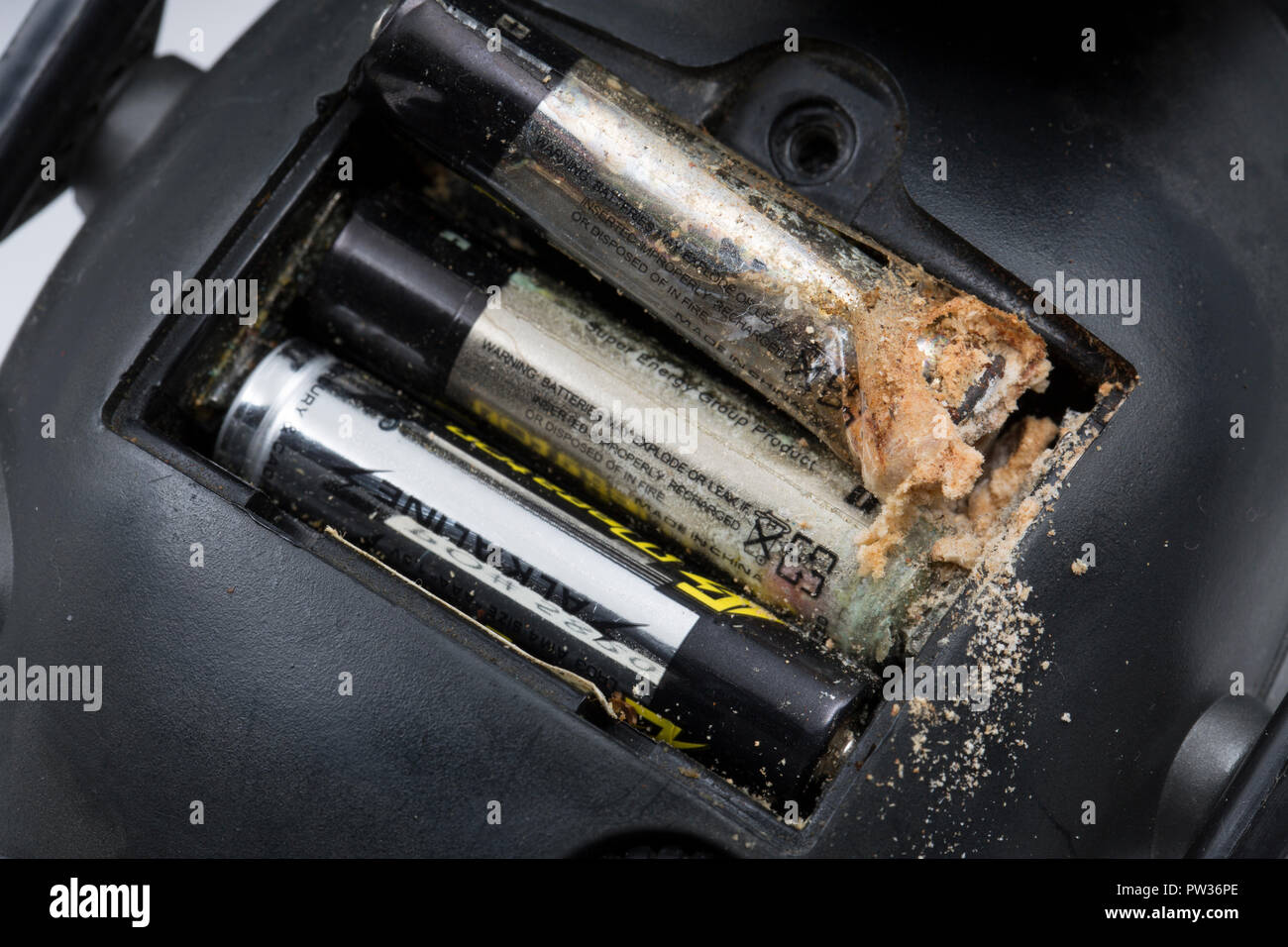 An alkaline AAA battery that has been left for several years in a pair of electronic hearing defenders and leaked from the negative end of the battery - Stock Image