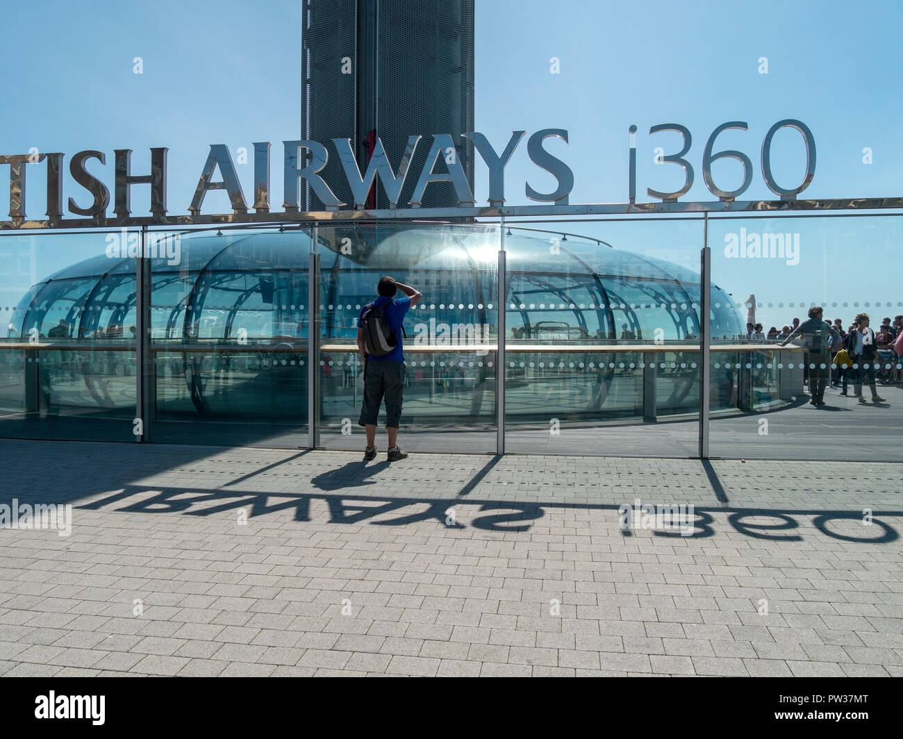 Sightseer looking through windows at the British Airways i360 observation pod, Brighton, East Sussex, England, UK - Stock Image