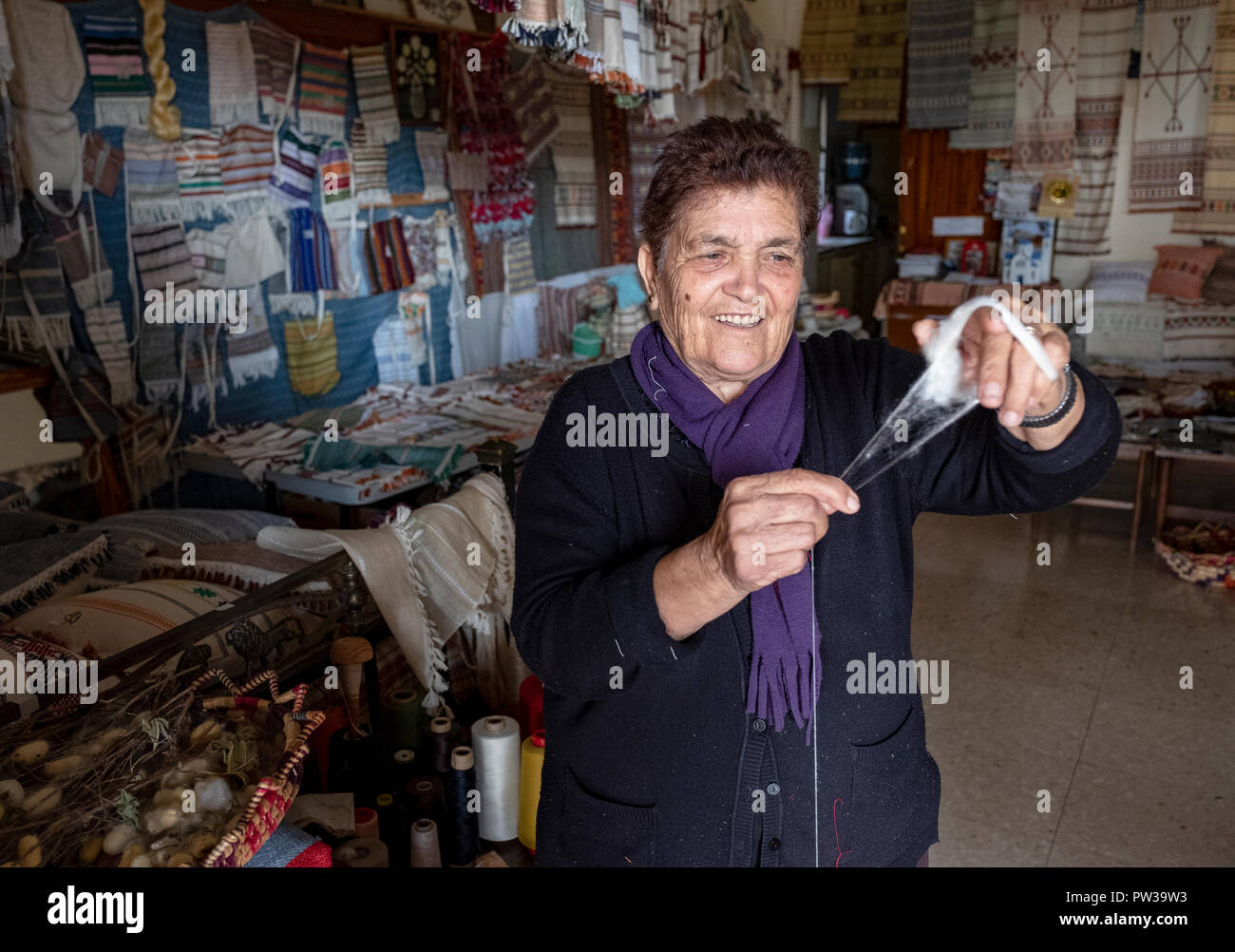 A woman holding cotton and explaining weaving methods at a Museum in Fyti village, Cyprus. - Stock Image