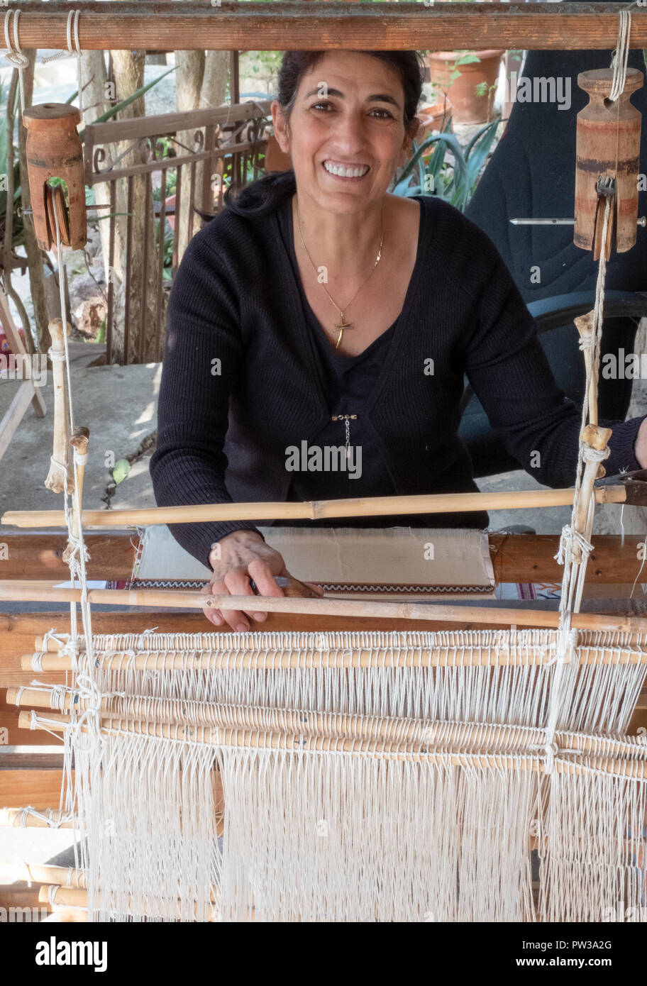 A woman using traditional weaving methods at a Museum in Fyti village, Cyprus. - Stock Image