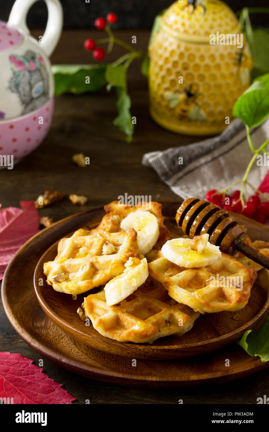 Thanksgiving baking. Belgian Walnut Wafers on a wooden kitchen table, served with fresh banana slices and honey. - Stock Image