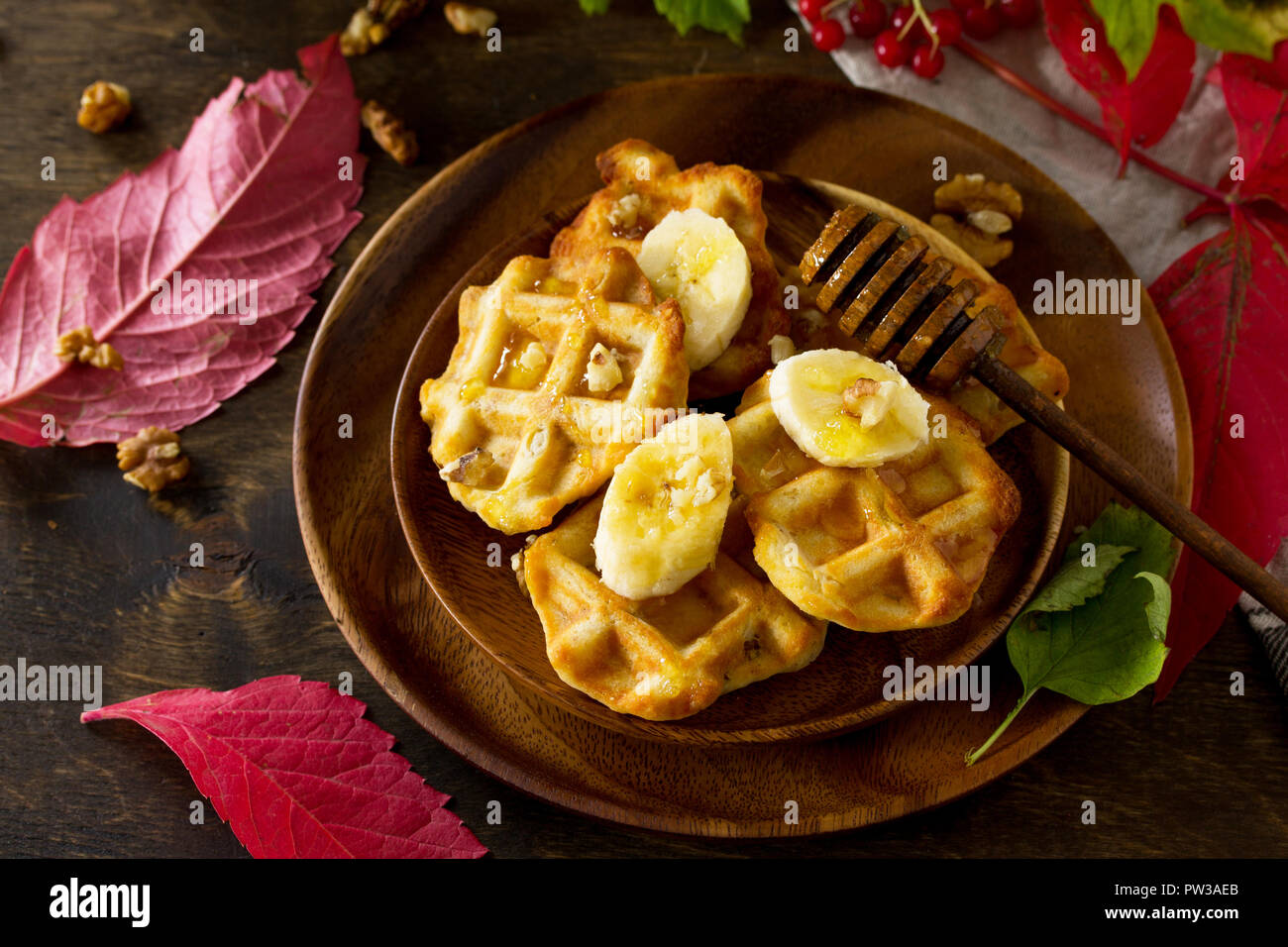Thanksgiving baking. Belgian Walnut Wafers on a wooden kitchen table, served with fresh banana slices and honey. Copy space. - Stock Image