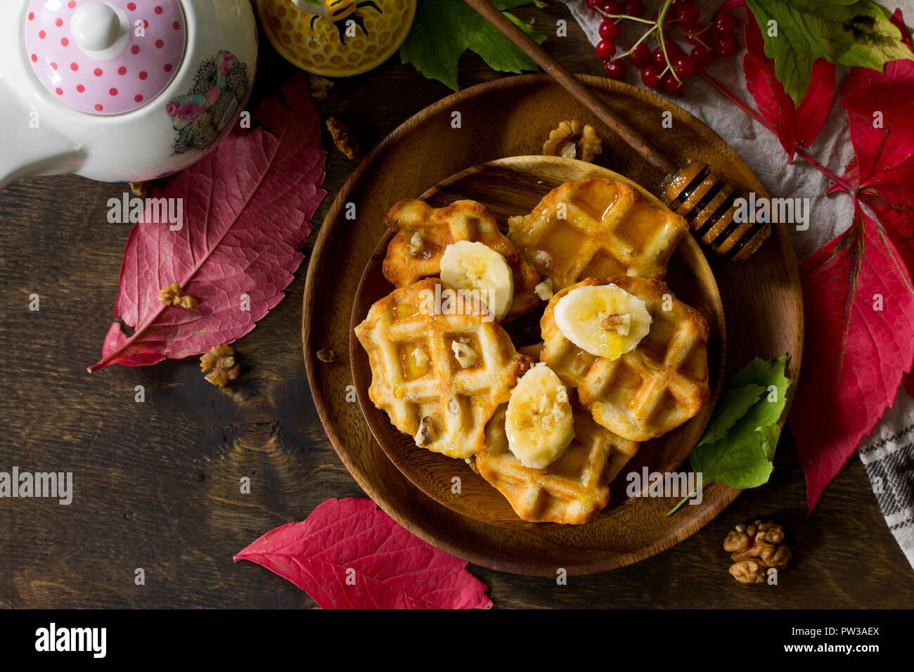 Thanksgiving baking. Belgian Walnut Wafers on a wooden kitchen table, served with fresh banana slices and honey. Top view flat lay background. Copy sp - Stock Image