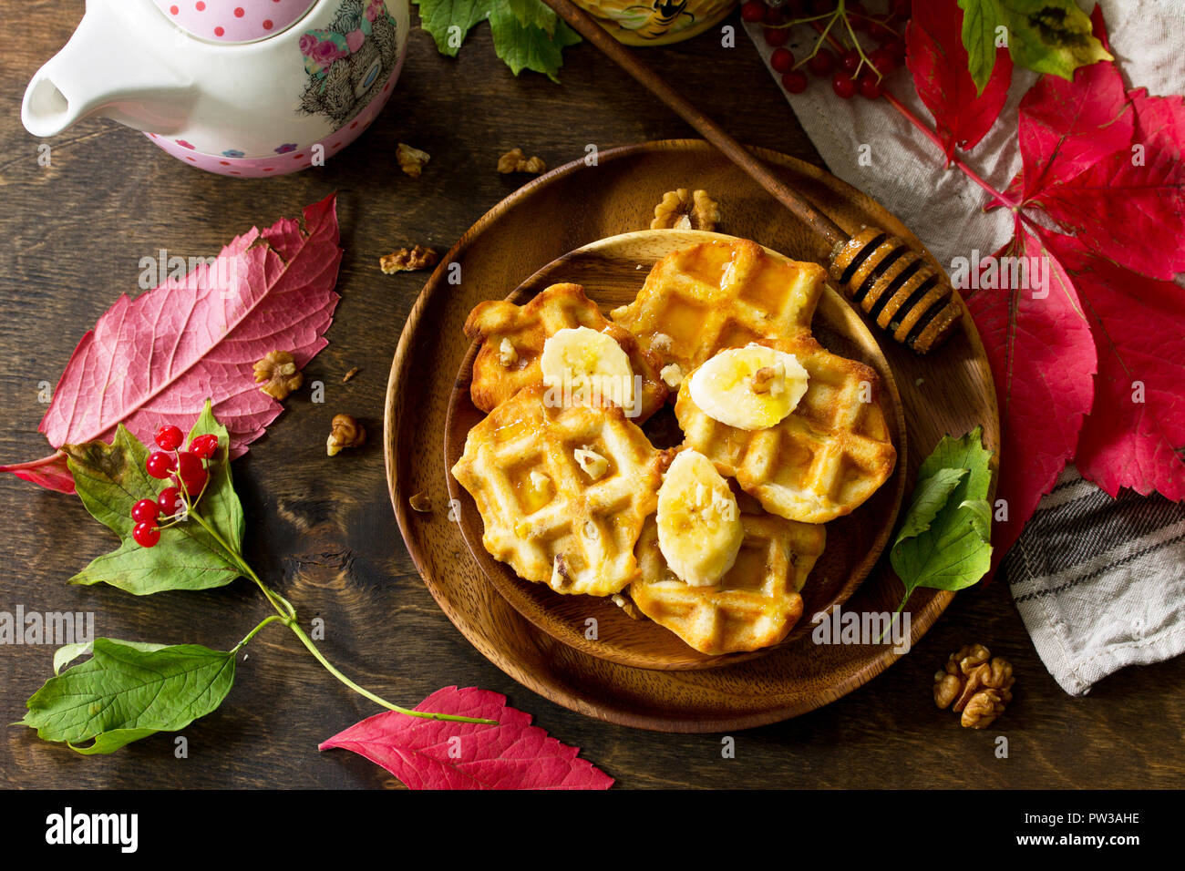 Thanksgiving baking. Belgian Walnut Wafers on a wooden kitchen table, served with fresh banana slices and honey. Top view flat lay background. - Stock Image