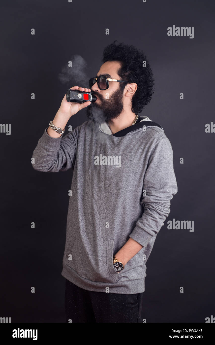 Vaping man holding a mod. A cloud of vapor. Black background. Vaping an electronic cigarette with a lot of smoke. Vape concept - Stock Image