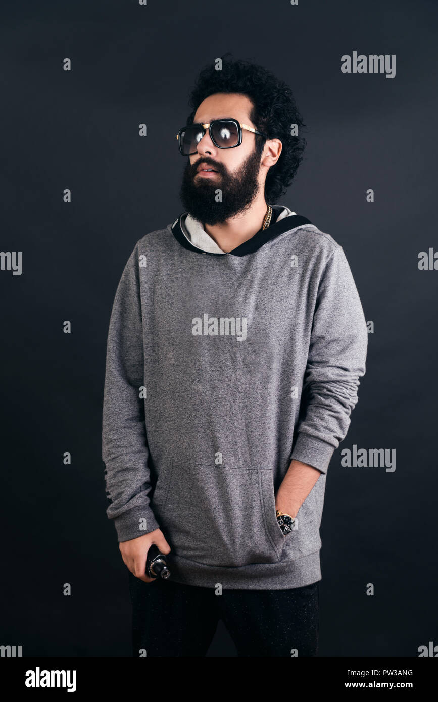 Thoughtful bearded young man with gray sweater and sunglasses. Man holding a mod. Black background. - Stock Image