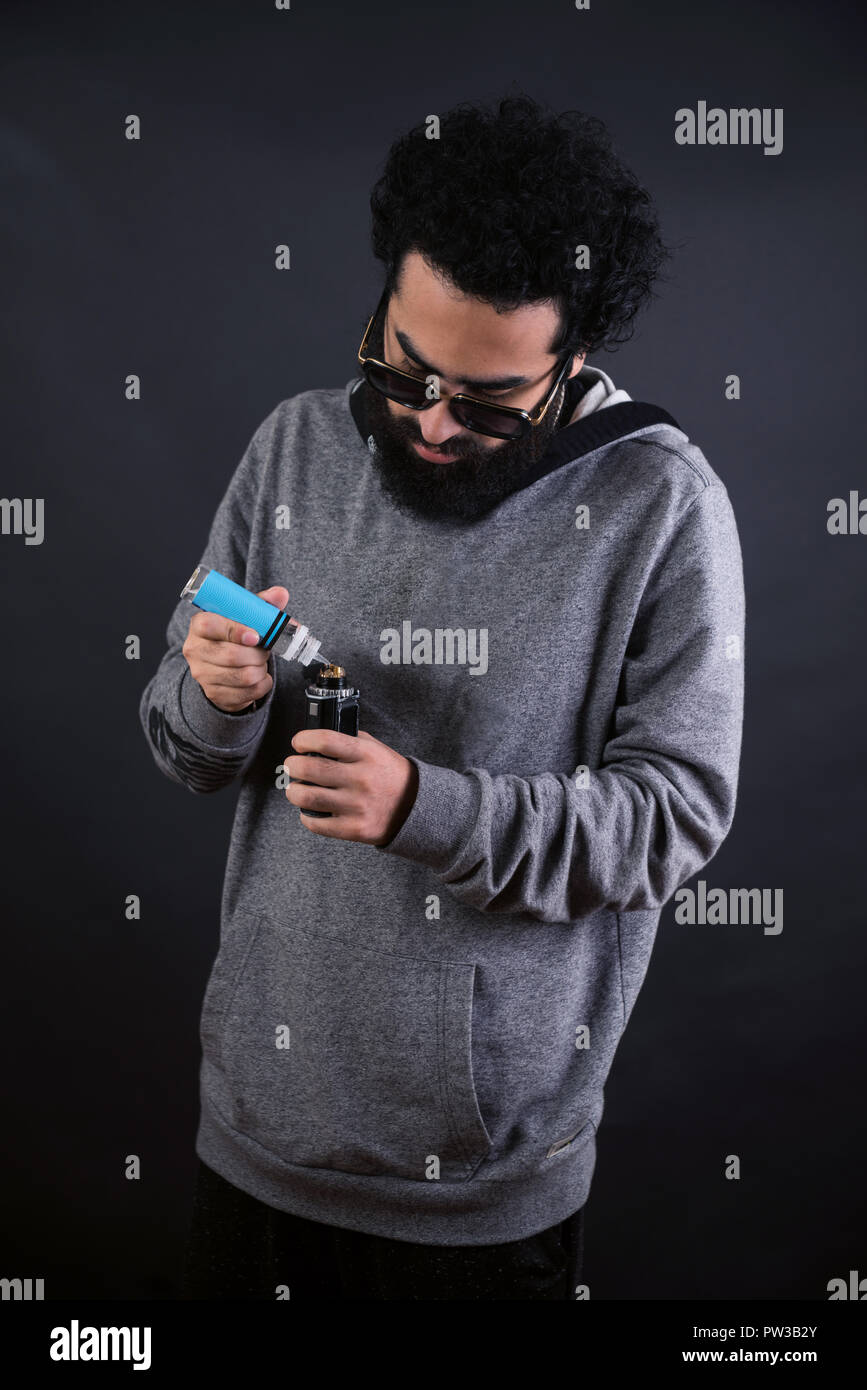 young vaper man with beard vaping mechanical mod. Guy smokes an electronic cigarette by blowing a smoke vapor. Holds in hand Refills rda juice from a bottle - Stock Image