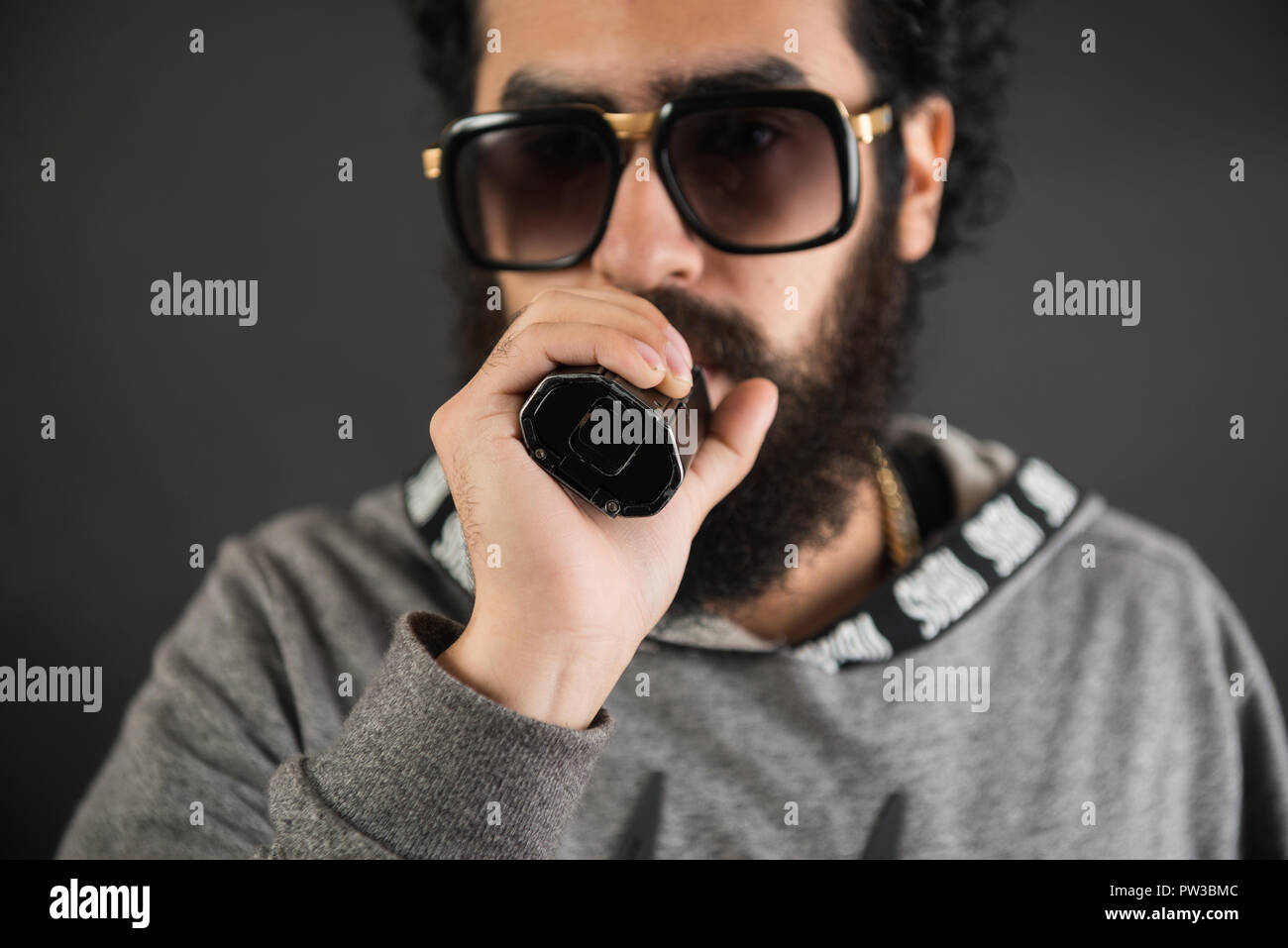 Portrait of a young guy with big beard and sunglasses and vaping an electronic cigarette on a black background. Stock Photo