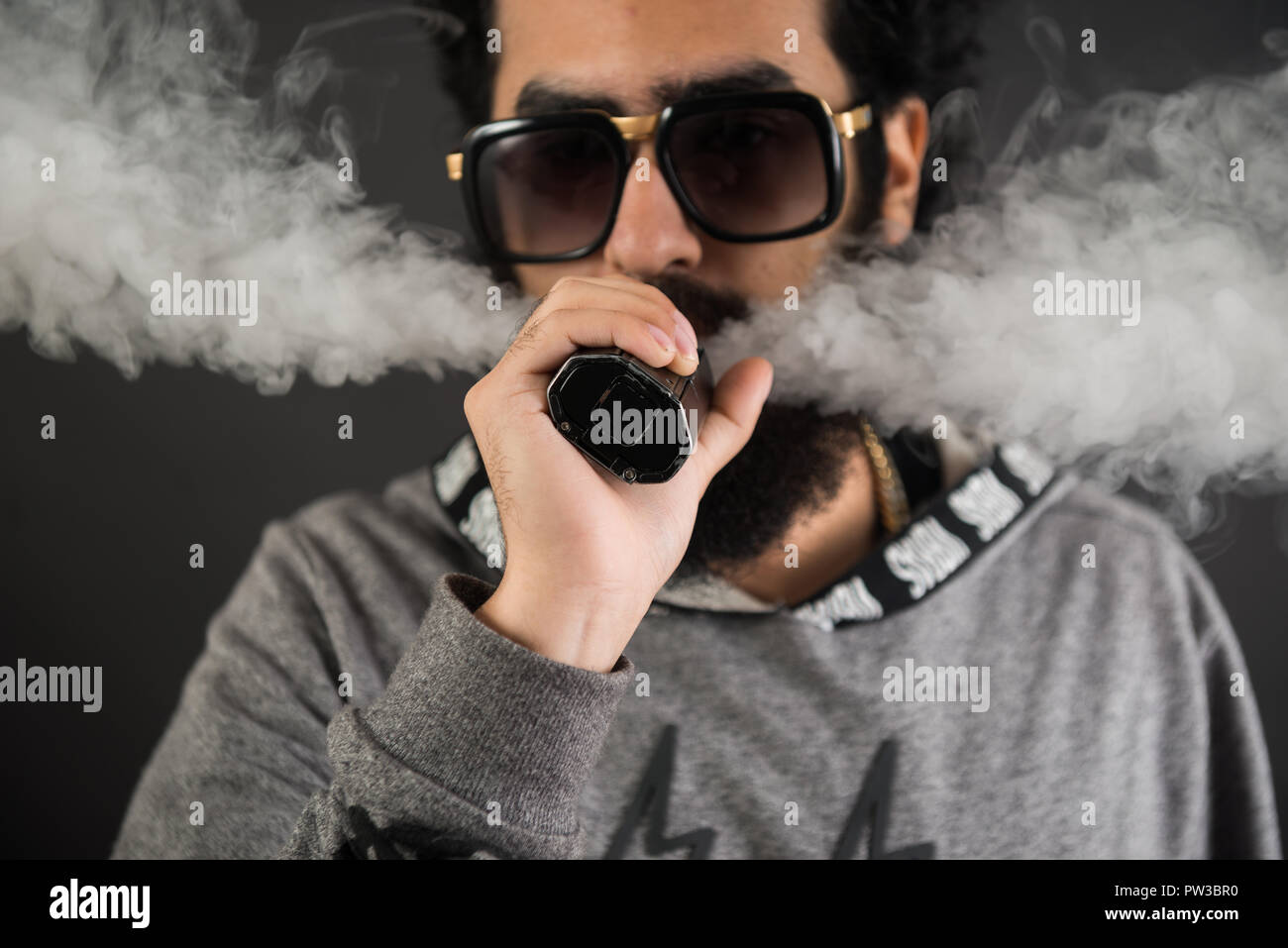 Portrait of a young guy with big beard and sunglasses and vaping an electronic cigarette on a black background. - Stock Image