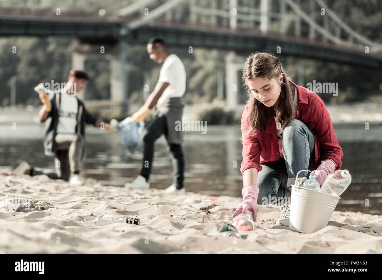 Beautiful first year student gathering empty bottles on the beach while volunteering Stock Photo