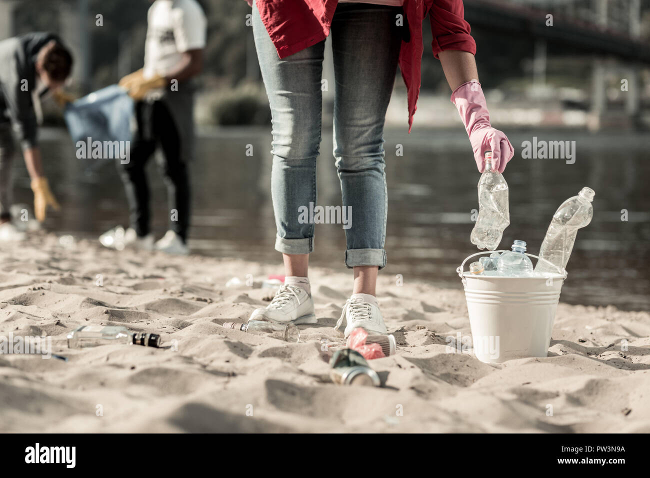 Active student volunteering while cleaning up trash left behind on the beach - Stock Image