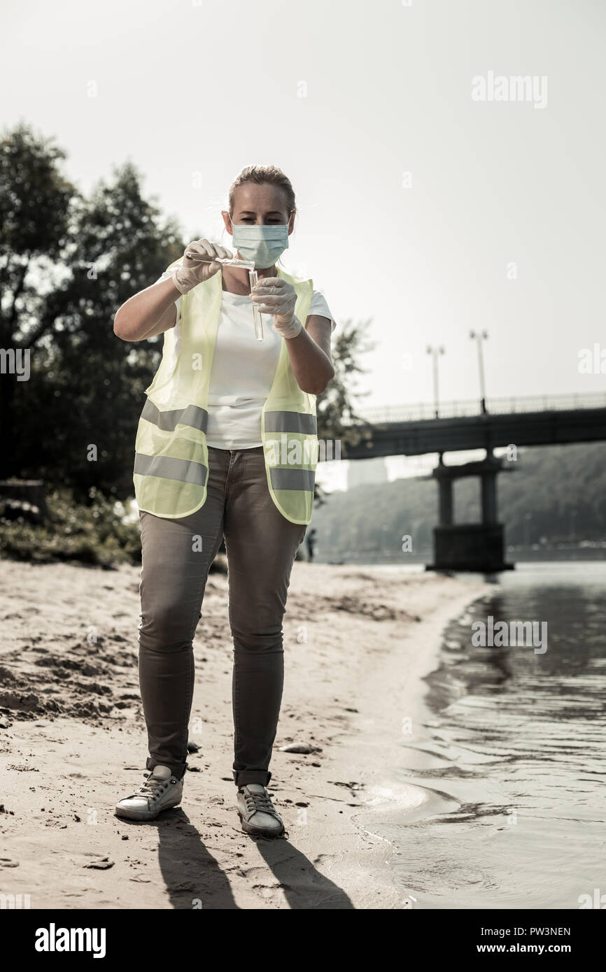 Worker of sanitary hygienic service wearing mask holding test tubes with river water - Stock Image