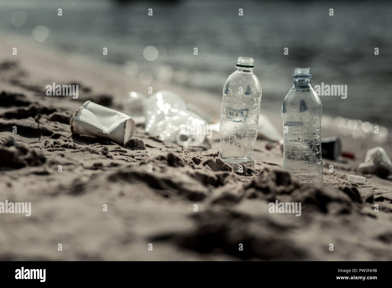 Close up of empty plastic bottles left behind by irresponsible people near the river - Stock Image