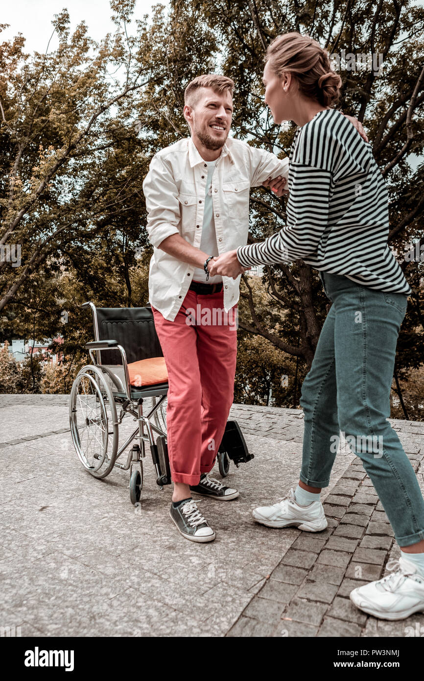 Reliable social worker helping her disabled patient to stand up - Stock Image