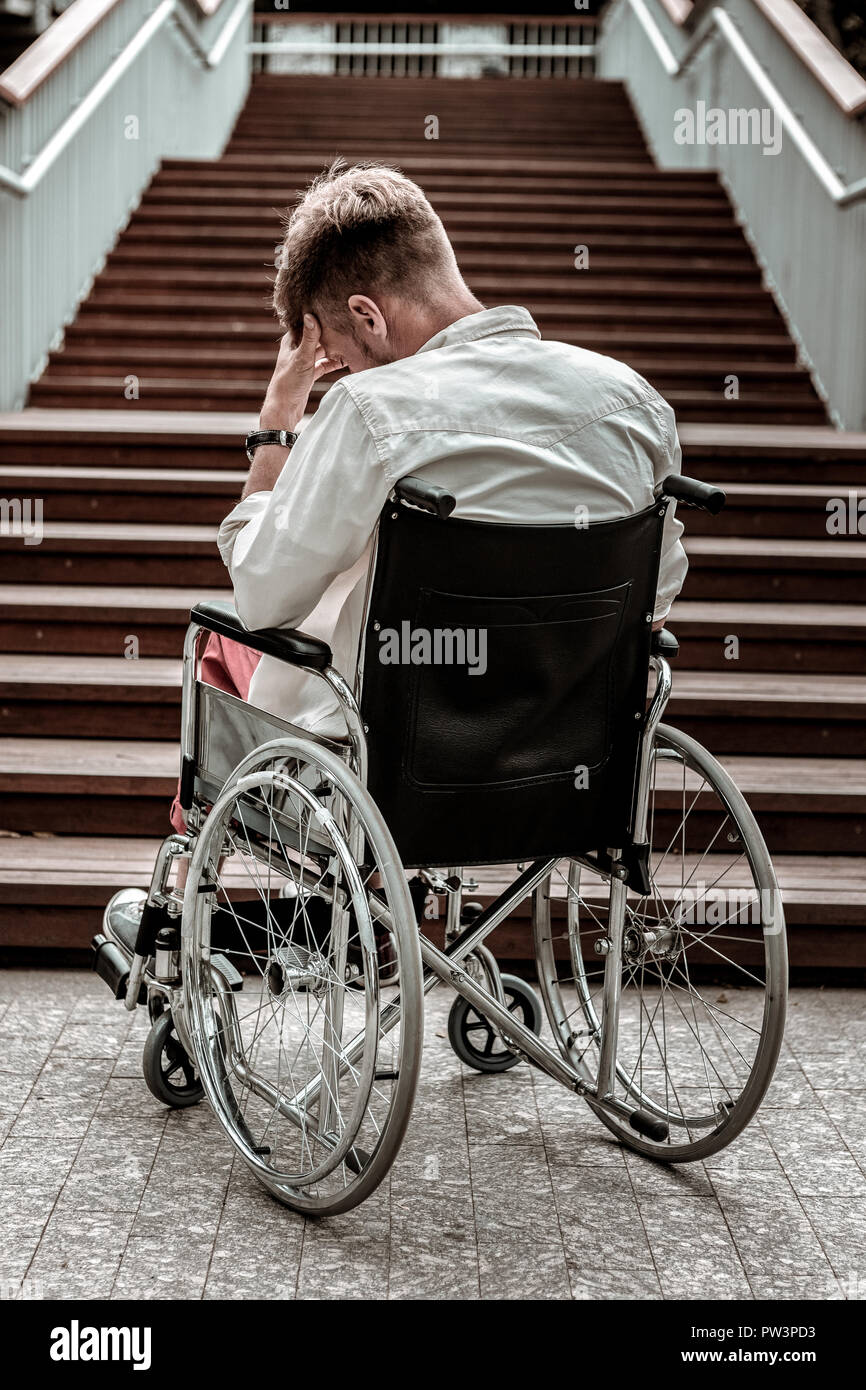 Invalid man closing his eyes and having difficulties - Stock Image