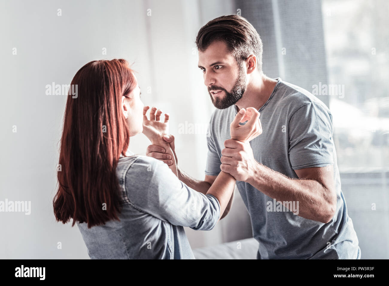 Angry emotional man holding his wifes hands - Stock Image