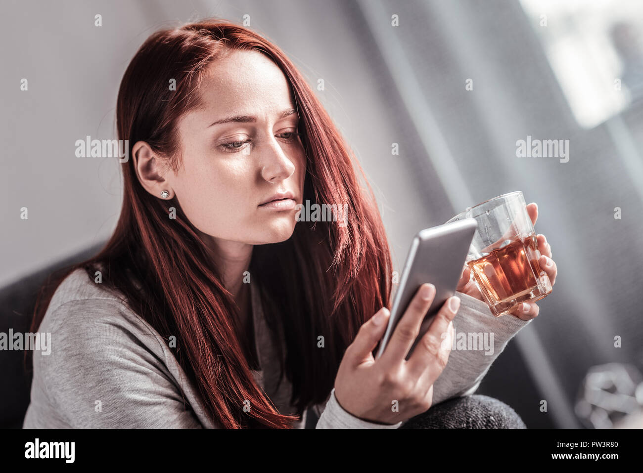 Depressed unhappy woman using her smartphone - Stock Image
